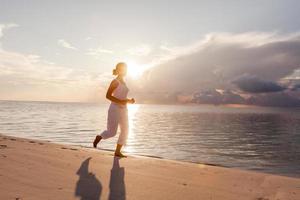 mujer caucásica trotar en la orilla del mar