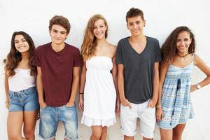 Retrato de grupo de adolescentes apoyado contra la pared