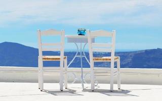 Las sillas en la parte superior de la casa, la isla de Santorini, Grecia