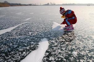 Little girl plays on ice of lake.
