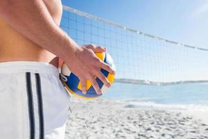 Handsome man holding volleyball photo