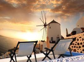 moinho de vento contra o pôr do sol colorido, santorini, grécia