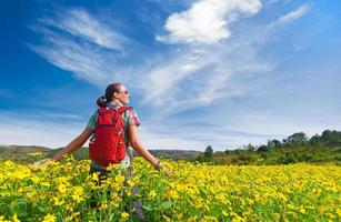 Young woman hiker walks on the background of colored fields.