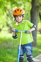 Boy in a safety helmet stands with kick scooter