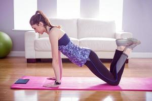 Fit woman doing press up on mat photo