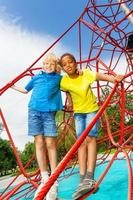Two boys stand hugging on red ropes of net photo