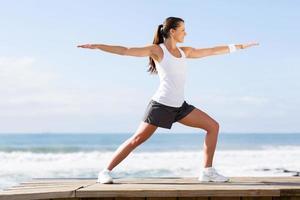 mujer joven haciendo yoga en la playa foto