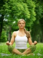 Woman sitting in yoga pose meditation outdoors photo