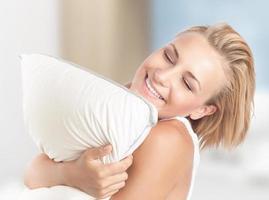 Happy girl enjoying pillow photo