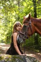 Hermosa niña y retrato de caballo marrón en bosque misterioso foto