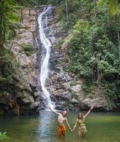 Pareja alegre disfrutando del baño del río por la cascada