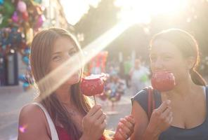 young women eating candy apple and enjoying