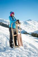 mujer joven con trineo disfrutando del sol de invierno