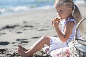 little girl enjoying a picnic on the beach photo