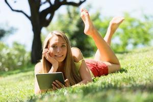 garota feliz, deitado na grama, aproveitando a leitura ereader