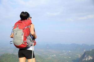 vrouw wandelaar geniet van het uitzicht bij zonsondergang bergtop