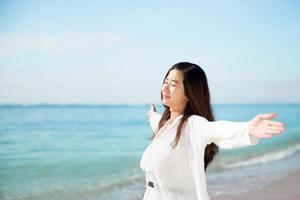 Asian woman enjoying beach, close eyes and open arms