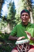 hombre tocando los tambores de mano en la naturaleza