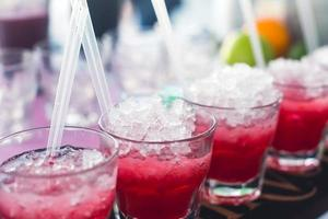 Line of different alcohol cocktails on event open-air night party