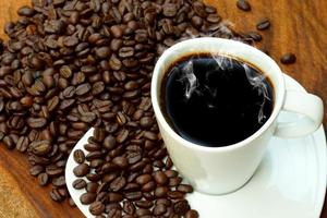 Coffee cup and beans on a wood background.