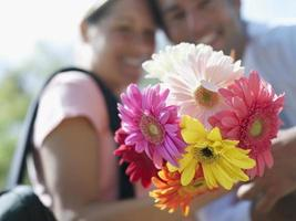 Couple holding bunch of colourful flowers, close-up, focus on fo