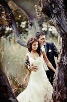 Happy bridal couple in forest. Summer wedding picture. photo