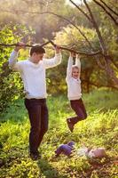 Dad helps support boy hanging on branch of tree,