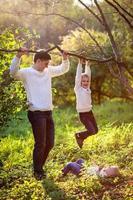 papá ayuda a apoyar al niño colgado de la rama del árbol