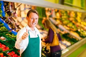 Smiling man in green apron with one thumb up at supermarket