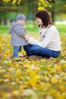 joven madre con su pequeño bebé en el parque otoño