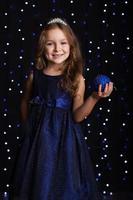 niña bonita niña está sosteniendo la bola de navidad azul