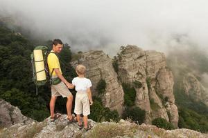 Backpacker with little son in the foggy mountains.