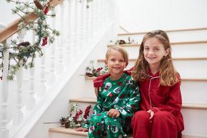 dois filhos sentados nas escadas de pijama no natal