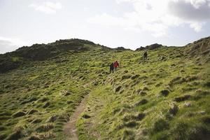 Three People Climbing Up Hill photo