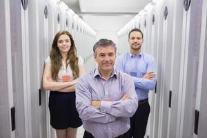 drie lachende mensen staan in het datacenter