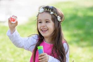Beautiful portrait of sweet lovely little girl blowing soap bubb photo