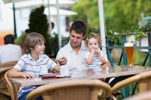 joven padre relajándose en la cafetería exterior con sus hijos