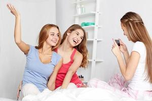 muchachas adolescentes con teléfono inteligente tomando fotos en casa