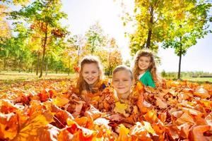Kids having fun laying on the ground with leaves photo