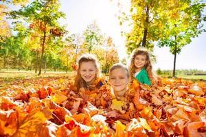 Niños divirtiéndose tirado en el suelo con hojas