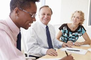 Three Businesspeople Having Meeting In Boardroom