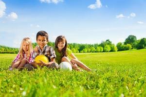 los niños se sientan en la hierba con pelotas deportivas foto