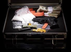 Case with money, gun and drugs photo