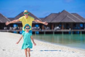 jeune père et petite fille sur la plage tropicale