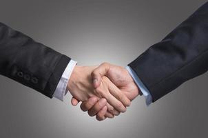 Hand shake between a businessman and a businesswoman on gray photo