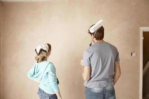 vista traseira do casal com rolo de pintura, olhando para a parede