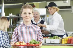 School aged boy posing with healthy lunch tray in cafeteria