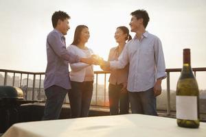 groep vrienden roosteren elkaar op het dak bij zonsondergang