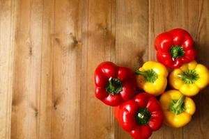 Red and yellow bell peppers on the wooden background
