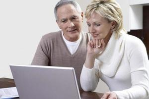 Middle-aged couple counting bills using laptop in kitchen photo